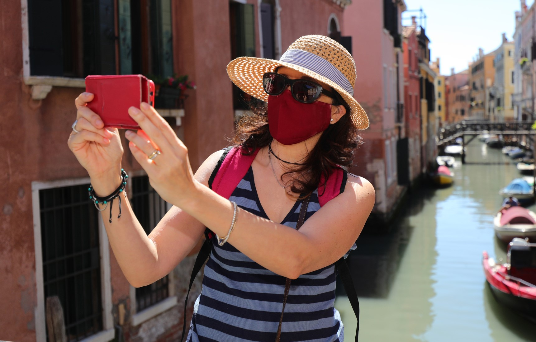 woman with straw hat while takes pictures of Venice and the surg